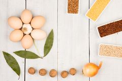 Various groats in bowls, eggs, bay leaf laid out in the shape of a flower on wooden table royalty free stock photo