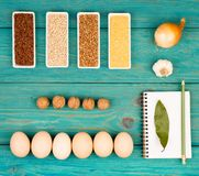 Various groats in bowls, eggs, bay leaf, onion, garlic, walnuts and notepad on blue table stock photo