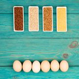 Groats in bowls and eggs on blue wooden table. Various groats in bowls and eggs on blue wooden table Stock Photography