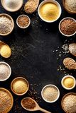 Various groats, cereals. Different types of groats in bowls and on a spoons on a black background, top view. royalty free stock photos