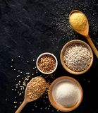 Various groats, cereals. Different types of groats in bowls and on a spoons on a black background, top view. stock photo
