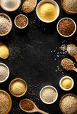 Various groats, cereals. Different types of groats in bowls and on a spoons on a black background, top view. stock photos