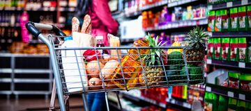 Various groceries in shopping cart. In grocery section of supermarket stock photos