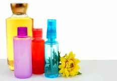 Various hair and body beauty products in bright colors with a cheerful yellow chrysanthemum royalty free stock images