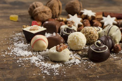 Various handmade chocolate on wood background. Festive background with candies, nuts, cookies on wooden table Stock Photo