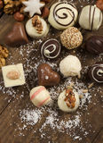 Various handmade chocolate on wood background. Festive background with candies, nuts, cookies on wooden table Royalty Free Stock Images