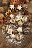 Various handmade chocolate on wood background. Festive background with candies, nuts, cookies on wooden table Royalty Free Stock Photos