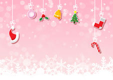 Various hanging Christmas ornaments on pink background with snowflake Stock Photo