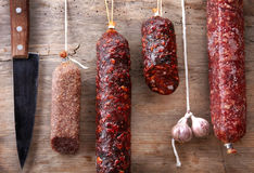 Various hanging salami sausages stock image