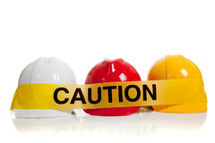 Various hard hats with caution tape. Various colored hard hats with caution tape Royalty Free Stock Photo