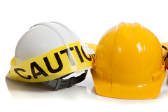 Various hard hats with caution tape Stock Images