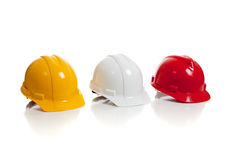 Various hard hats on a white background Stock Images