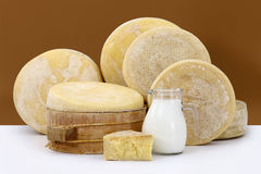 Various hard parmesan cheese on the white table with a jug milk Stock Photos