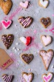 Various heart shaped cookies with love tag on grey cracked surface. Top view of various heart shaped cookies with love tag on grey cracked surface Royalty Free Stock Photo