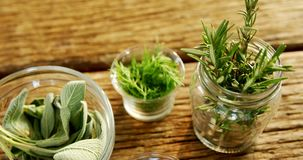Various herbs in a jar on wooden table 4k