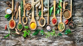 Various herbs and spices for cooking on old wooden board. Colourful aromatic various herbs and spices for cooking on old wooden board Royalty Free Stock Photo