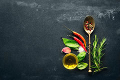 Various herbs and spices. Herbs and spices with old metal spoon on slate background stock image