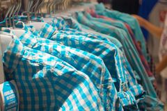 Various hipster shirts on hangers in store. Stock Photography