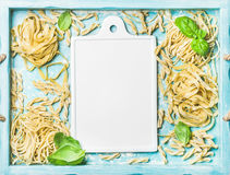 Various homemade fresh uncooked Italian pasta and white ceramic board Royalty Free Stock Photography