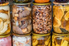 Pickled spicy mushrooms at village marketplace. Various homemade pickled mushrooms are a part of Russian traditional cuisine Stock Photo