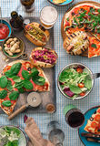 Various homemade pizza, different hot dogs, wine, beer and snack. Various homemade pizza, different hot dogs, red wine, beer and snack for beer on the table, top royalty free stock photo