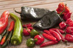 Various hot peppers scattered on cutting board Stock Images