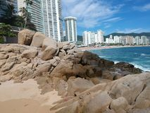 Acapulco Beach line with big stones. Various hotels along the shoreside of Acapulco with big stones and palms Royalty Free Stock Image