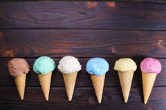 Various ice cream cones on wooden table, flat lay Royalty Free Stock Photos
