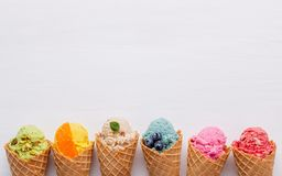 Various of ice cream flavor in cones blueberry ,strawberry ,pistachio ,almond ,orange and cherry setup on white wooden background. Summer and Sweet menu stock photos