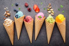 Various of ice cream flavor in cones blueberry ,strawberry ,pistachio ,almond ,orange and cherry setup on dark stone background . Summer and Sweet menu concept stock images