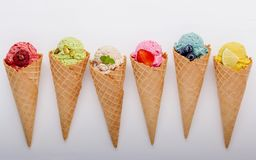 Various of ice cream flavor in cones blueberry ,strawberry ,pistachio ,almond ,orange and cherry setup on white wooden background. Summer and Sweet menu stock photography