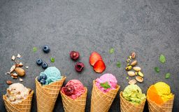 Various of ice cream flavor in cones blueberry ,strawberry ,pist. Achio ,almond ,orange and cherry setup on dark stone background . Summer and Sweet menu concept Stock Image