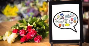 Various icons on digital tablet by flowers on table Royalty Free Stock Image