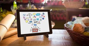 Various icons and text in digital tablet by basket and paper on table Stock Photography