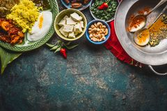 Various indian food bowls with curry, yogurt ,rice,bread , chicken,chutney, paneer cheese and spices on dark rustic background, to. P view, border Stock Photo