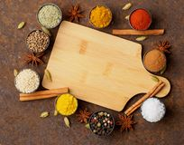 Various Indian spices in metal cups. Empty wooden Board, top vie. W, space for text Stock Photo