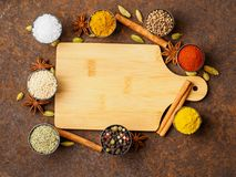 Various Indian spices in metal cups. Empty wooden Board, top vie Stock Photos