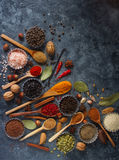 Various indian spices, nuts and herbs in wooden spoons and metal bowls stock photos