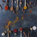 Various indian spices in wooden spoons and metal bowls and nuts on dark stone table. Colorful spices, top view royalty free stock image