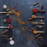 Various indian spices in wooden spoons and metal bowls and nuts on dark stone table. Colorful spices, top view. Various indian spices in wooden spoons and metal stock photos