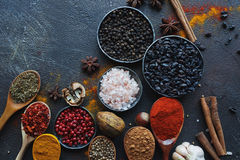 Various indian spices in wooden spoons and metal bowls and nuts on dark stone table. Colorful spices, top view royalty free stock photography