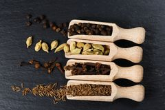 Various of spices and herbs in wooden spoons. Flat lay of spices on black stone royalty free stock photo