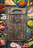 Various ingredients for bruschetta or crostini making: smoked meat, Sausage, ham ,pesto, dry tomatoes, peperoni around blank old c. Utting board on rustic royalty free stock photo