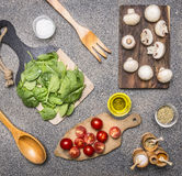 Various ingredients for cooking vegetarian dishes, mushrooms, spinach leaves, cherry tomatoes seasonings on rustic background Royalty Free Stock Image
