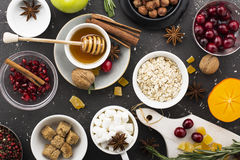 Various ingredients for winter seasonal baking and other recipes, pomegranate, honey, orezhi, apples, persimmons, herbs Stock Photo