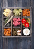Various Italian pasta, cherry tomatoes in  wooden  vintage box Stock Photography