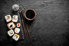 Various Japanese rolls with soy sauce and chopsticks. On black rustic background royalty free stock photo