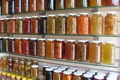 Various jars with fruit jam on glass shelves Stock Photography