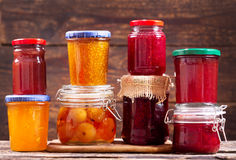 Various jars of fruit jam on wooden table Royalty Free Stock Photo