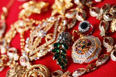 Various jeweleries. Many jeweleries with colorful gems on red cloth, selective focus on pendant Royalty Free Stock Photos